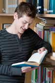 Happy student reading book in a library — Stock Photo