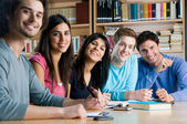 Smiling group of students in a library — Stock Photo