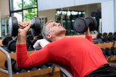 Exercising with dumbells at gym — Stock Photo