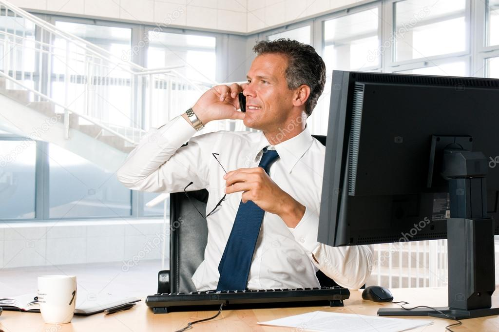 Succesful businessman sit at his desk while talking on mobile — Stock Photo #12656319