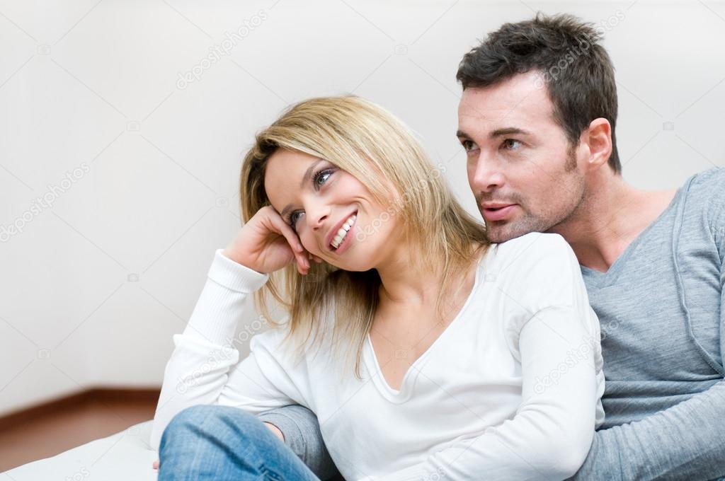 Young dreaming couple sitting in their living room and looking away at their future — Stock Photo #12657496