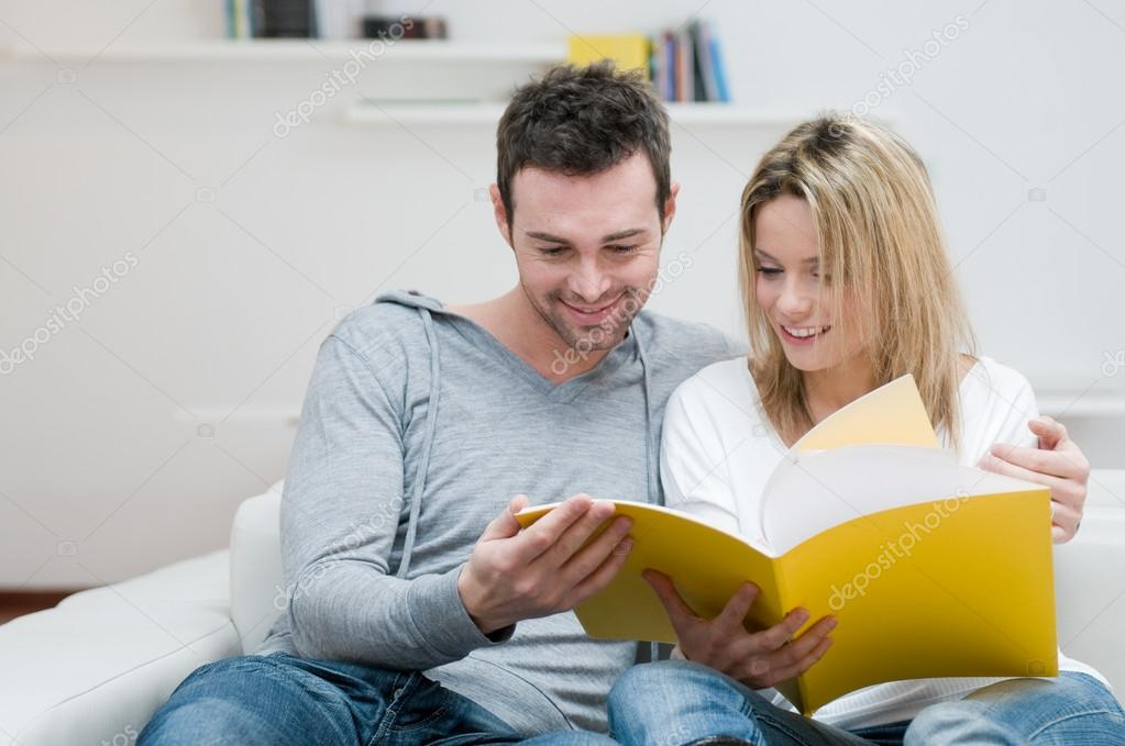 Young couple reading together a magazine in their living room at home — Stock Photo #12657503