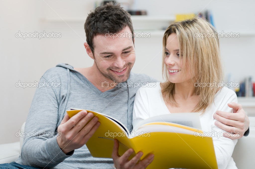 Young couple reading together a magazine in their living room at home  Stock Photo #12657508