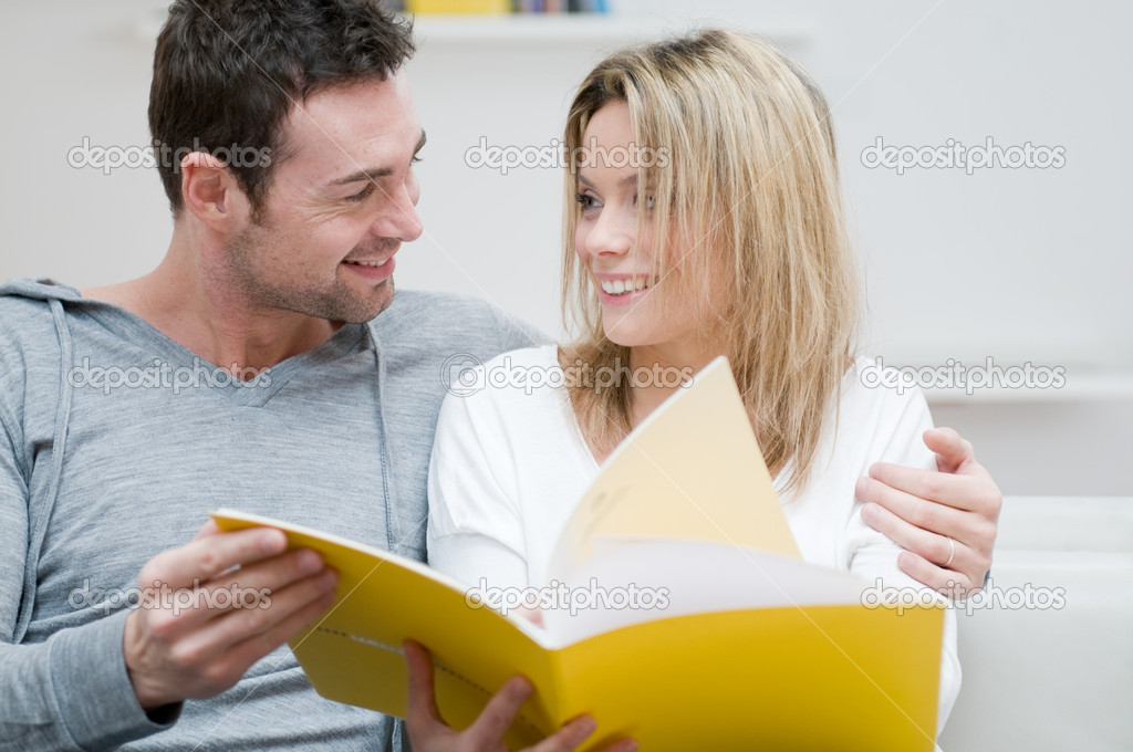 Young couple reading together a magazine and looking each other in their living room at home — Stock Photo #12657511