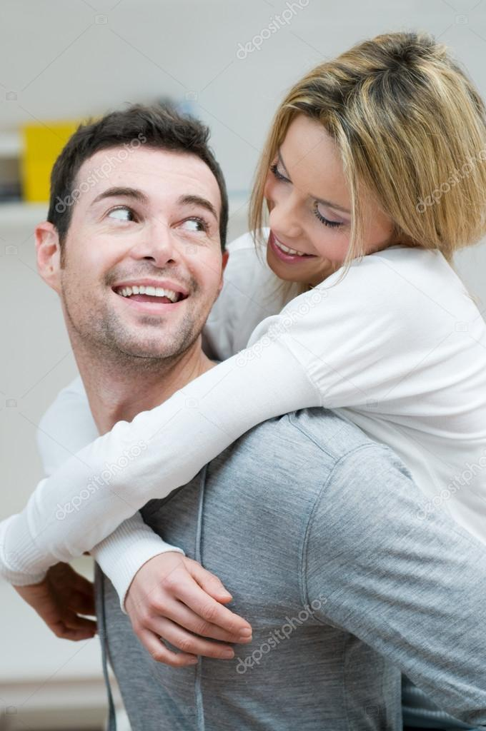 Young couple piggybacking and have fun at home with knowing glance  Stock Photo #12657538