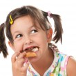 Little girl biting a snack - Stock Photo