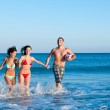 Smiling friends playing at beach — Stock Photo #12661346