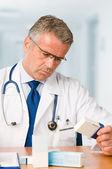 Doktor ilaç servis talepleri inceleyerek — Stok fotoğraf