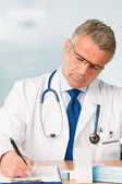 Mature doctor prescribes medical exam — Stok fotoğraf