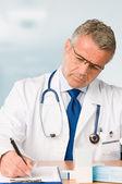Starší lékař předepisuje lékařské vyšetření — Stock fotografie