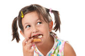 Little girl biting a snack — Stock Photo