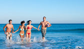 Smiling friends playing at beach — Stock Photo