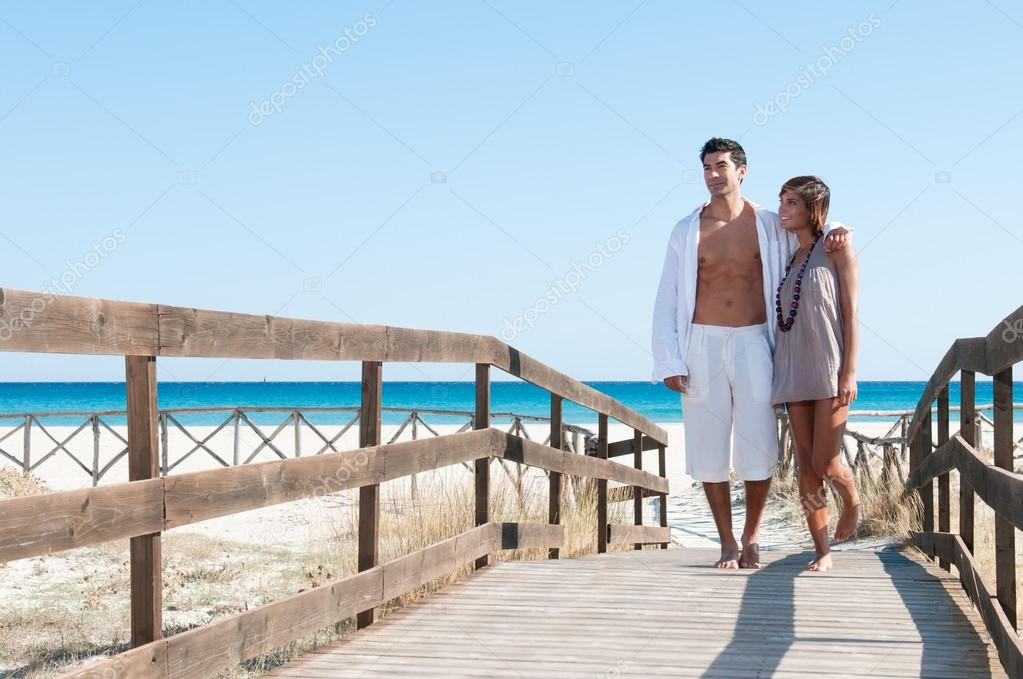 Happy beautiful young couple walking together at summer tropical beach — Stock Photo #12661218