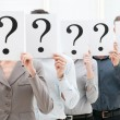 Business team behind question marks - Stock Photo