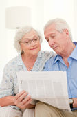 Aged couple reading news — Stock Photo