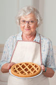 Senior lady with homemade cake — Stock Photo