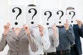 Equipo de negocios detrás de signos de interrogación — Foto de Stock