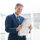 Satisfied businessman read newspaper — Stock Photo