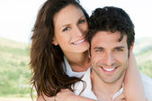 Loving couple piggyback — Stock Photo