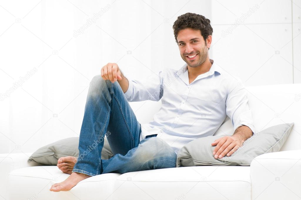 Happy smiling man relaxing and sitting on sofa at home — Stock Photo #12765213