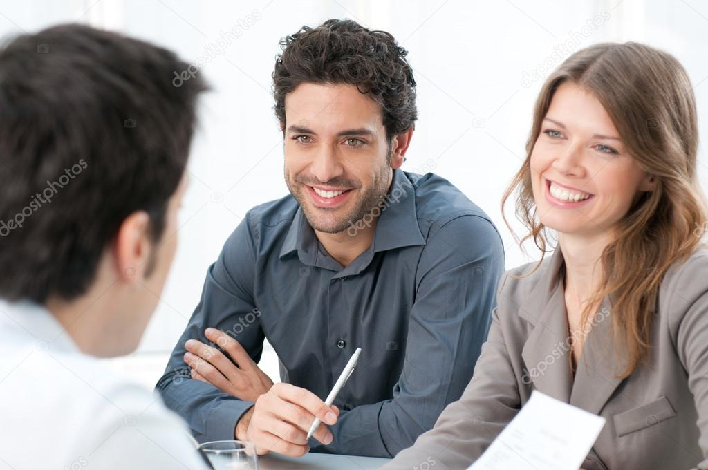 Smiling businessman and colleagues working together on documents at office  Foto Stock #12766788