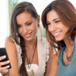 Stok fotoğraf: Two Women Looking At Mobile Phone