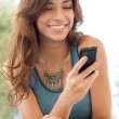 Woman Smiling And Holding Mobile Phone — Stock Photo