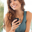 Woman Smiling And Holding Cell Phone - Stock Photo