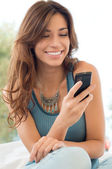 Woman Smiling And Holding Mobile Phone — Stok fotoğraf