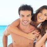 Happy couple piggyback at beach — Stock Photo