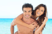 Happy couple piggyback at beach — Stockfoto