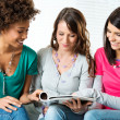 Stock Photo: Young Women Reading Magazine