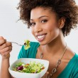African American Woman Eating Salad - Stock Photo