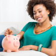 Woman Putting Coin In Piggybank - Foto Stock
