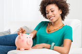 Woman Putting Coin In Piggybank — Foto de Stock