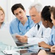 Team Of Doctors Examining Reports - Stock Photo