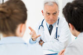 Doctor discussing with patients — Stockfoto