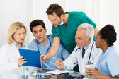 Team Of Doctors Examining Reports — Stockfoto
