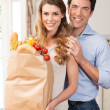 Couple With Grocery Bag In Kitchen — Stock Photo #28206785