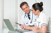 Doctor and nurse working at laptop — Stock Photo