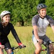 Young Couple Riding Bicycle In Meadow — Stock Photo