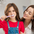 Girl With Her Mother Brushing Teeth — Stock Photo