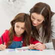 Foto Stock: Mother Helping Her Daughter While Studying