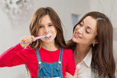 Girl With Her Mother Brushing Teeth — Стоковое фото