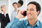 Uomo d'affari sorridenti parla cellulare — Foto Stock