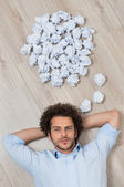 Young Man Lying On Floor With Crumpled Papers — Stock Photo