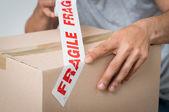 Hombre caja sellado con adhesivo frágil — Foto de Stock