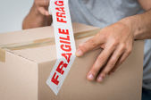 Man Sealing Box With Fragile Adhesive — Stock Photo