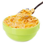 Bowl and spoon with corn flakes on the white background — Stock Photo