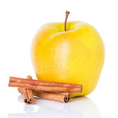 Ripe yellow apple with cinnamon sticks — Stock Photo